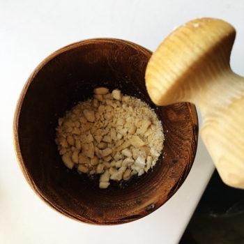 Часть орехов измельчить в ступке до состояния крошки.