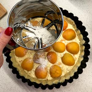 Чтобы абрикосы закарамелизировались и не сгорели во время приготовления, посыпаем сахарной пудрой.